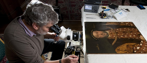 Dendrochronologist examines the wooden panels of Longleat's Henry VIII portrait banner. Pic: BNPS